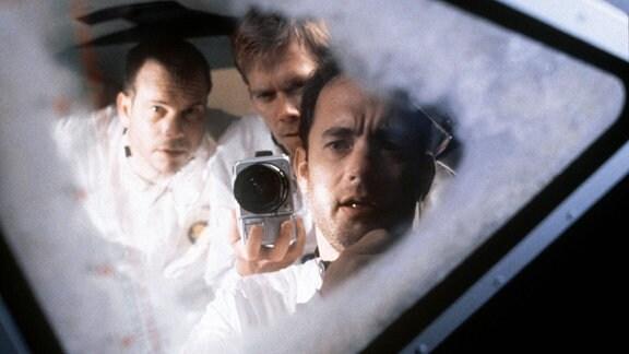Szene aus dem Film ''Apollo 13''. Die Astronauten schauen zum Fenster hinaus auf den Mond.