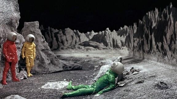 Szene aus dem Film ''Moon Zero Two''. Zwei Astronauten finden auf der Mondoberfläche einen am Boden liegenden Astronauten.