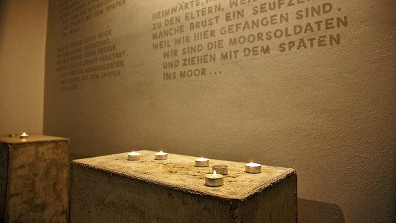 Kerzen brennen im Gedenkraum vor dem in die Wand eingravierten Lied der Moorsoldaten