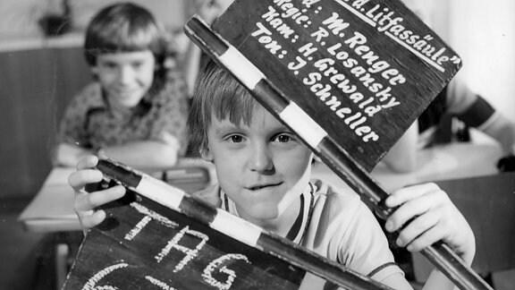 Schwarzweiß-Bild eines Jungen mit Filmklappe.