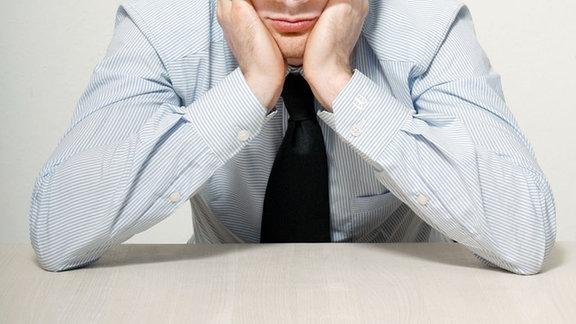ein Mann sitzt den Kopf in die Hände gestützt am Tisch.