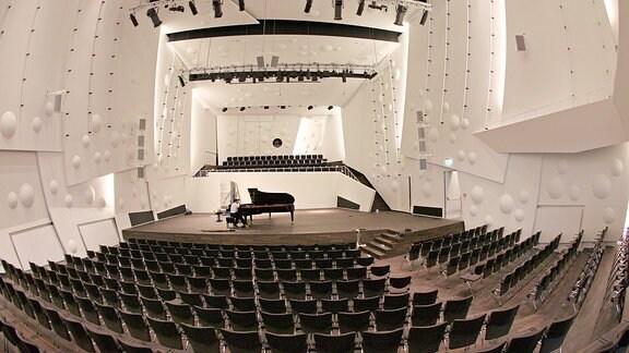 Ein Klavierstimmer sitzt im neuen Konzertsaal der Musikhochschule in Dresden am Flügel.