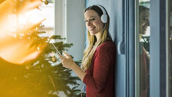 Eine junge FRau steht mit Kopfhörern neben einem Weihnachtsbaum