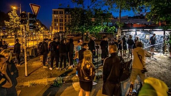Menschen stehen vor einem Club in einer Schlange.