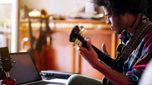 Ein Musiker übt zuhause auf seiner Gitarre. Vor ihm auf dem Couchtisch steht ein Laptop.