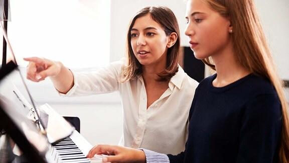 Zwei Mädchen spielen Klavier.