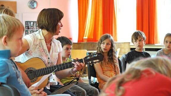 Schüler mit einer Lehrerin beim Musikunterricht