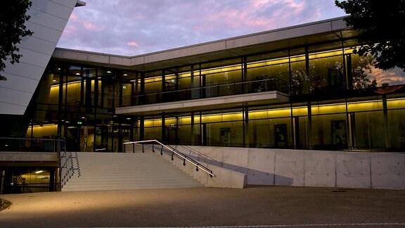 Eingang zum Konzertsaal der Hochschule für Musik Carl Maria von Weber in Dresden: Zweigeschossiger moderner Bau mit auslandender Treppe bei Dämmerung. Gelbe Lichter, im Hintergrund leicht rosafarbener Himmel. Links im Anschnitt Konzertsaalbau.