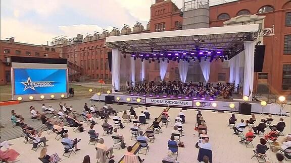 Orchester mit Publikum vor altem Gebäude