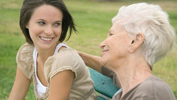 Eine jüngere und eine ältere Frau lächeln einander an