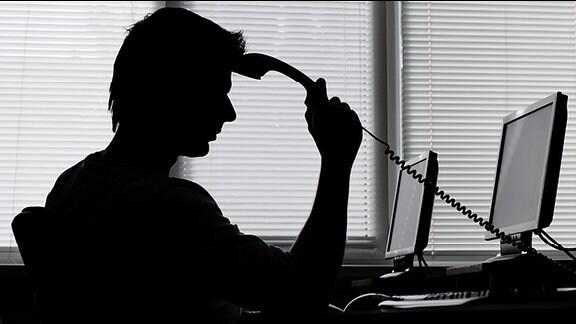 Ein Mann mit einem Telefonhörer in der Hand in nachdenklicher Pose vor einem Computer
