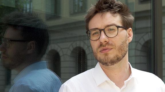Ein Mann steht vor einer Glasscheibe und blickt in die Kamera.