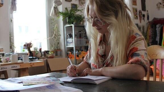 Eine Frau malt etwas in ein Heft.