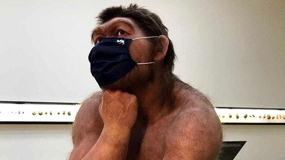 Das Modell eines Neandertalers aus dem Landesmuseum in Halle, das einen Mundschutz trägt