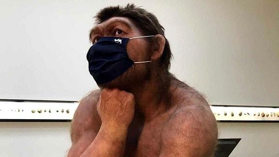 Das Modell eines Neandertalers aus dem Landesmuseum in Halle, das einen Mundschutz trägt: Urzeitlicher Mensch mit gedrungenem Körperbau und stärkerer Körperbehaarung, hockt mit Blick nach schräg oben, Kopf auf Faust gestützt.