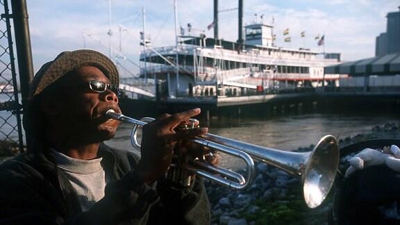 Ein Straßenmusiker spielt am Pier der Toulouse Street Wharf im French Quarter in New Orleans (Louisiana, USA) auf seiner Trompete