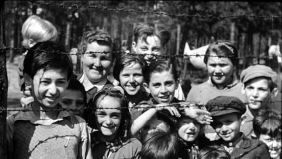 Lächelnde Kinder hinter Stacheldraht, aufgenommen von Sergeant Mike Lewis am 19./20. April 1945.