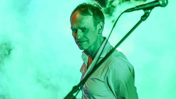 Ein Mann steht auf einer Konzertbühne hinter einem Mikrophon.