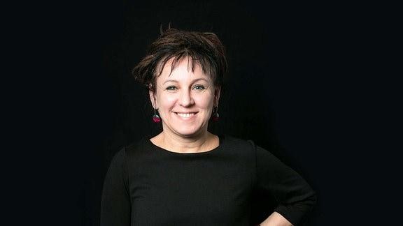 Autorin Olga Tokarczuk posiert lächelnd für ein Foto.