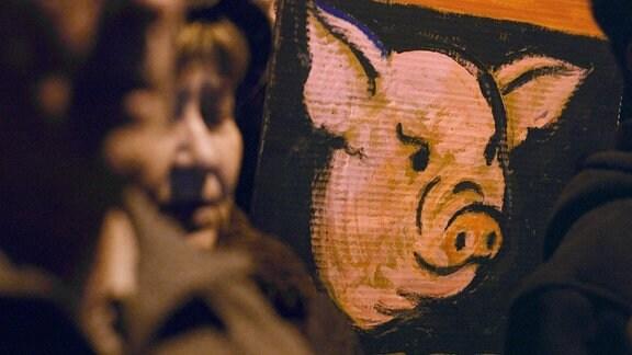 Ein gemalter Schweinekopf auf einem Demonstrationsschild.