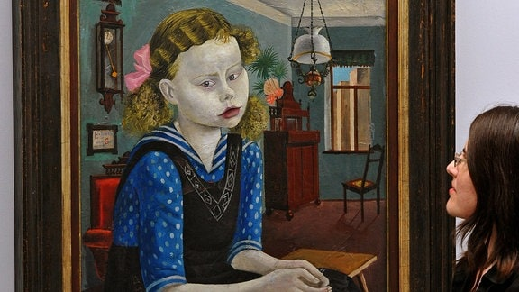 Eine Frau betrachtet das Gemälde 'Mädchen am Sonntag' von Otto Dix.