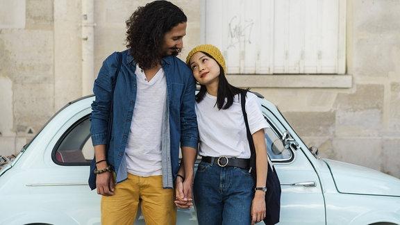 Ein Paar steht vor einem Auto und schaut sich verliebt an.