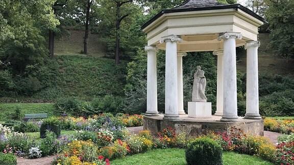 Ein kleiner Pavillon mit einer Frauenskulptur steht inmitten von Blumenrabatten