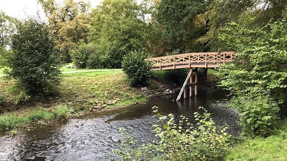 Eine Holzbrücke führt über einen Fluss.