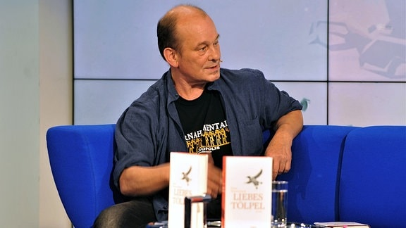 """Peter Wawerzinek sitzt auf dem Blauen Sofa und stellt """"Liebestölpel"""" vor."""