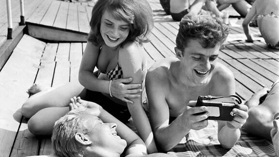 1963, Menschen hören Musik aus einem Transistorradio