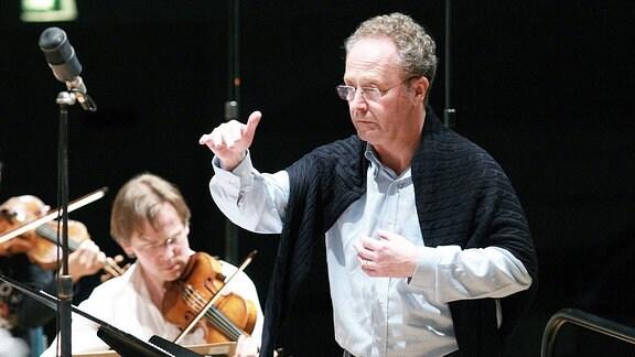 Ein Mann steht inmitten eines Orchesters und dirigiert dieses.