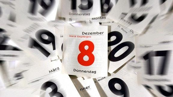 Leicht verwackelte Ansicht eines Stapels von abgerissenen Kalenderblättern