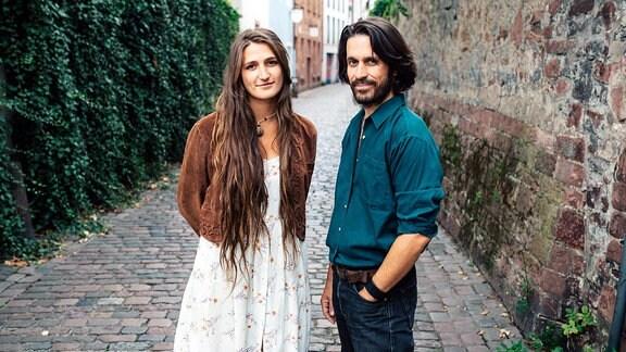 Eine Frau und ein Mann stehen auf einem Gehweg aus Pflastersteinen. Rechts von ihnen eine alte Stadtmauer, linkerhand eine mit Efeu überwachsene Wand. Beide schauen lächelnd in die Kamera.