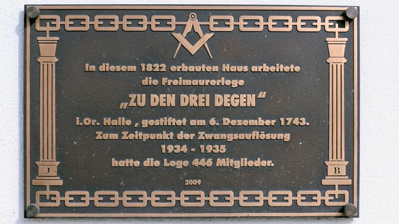 Erinnerungstafel mit goldener Schrift und Symbolen auf schwarzem Untergrund