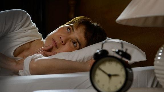 Mann im Bett mit offenen Augen hinter dem Nachttisch mit Wecker