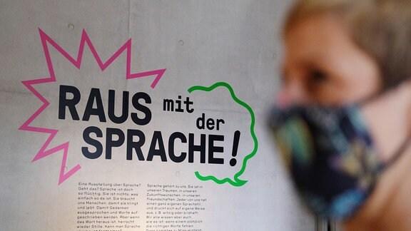 """Eine Frau mit Mundschutz steht in der Ausstellung """"Raus mit der Sprache"""" in Luthers Sterbehaus"""