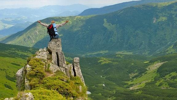 Woman in montains auf Felsen mit Rucksack mit seinen Armen gespreizt