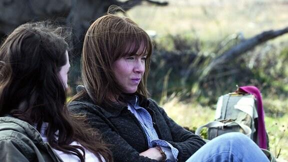 Filmszene. Zwei Frauen sitzen nebeneinander im freien neben einem Baum.