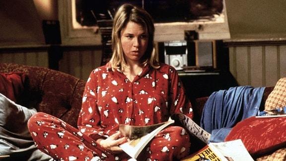 Filmszene. Eine Frau sitzt in einem roten Schlafanzug auf einem Bett.