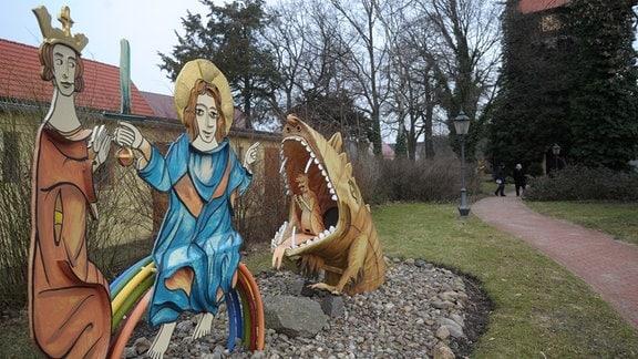 Figuren der Bilderhandschrift von Eike von Repgow stehen an der Dorfkirche, in Reppichau (Landkreis Anhalt-Bitterfeld).
