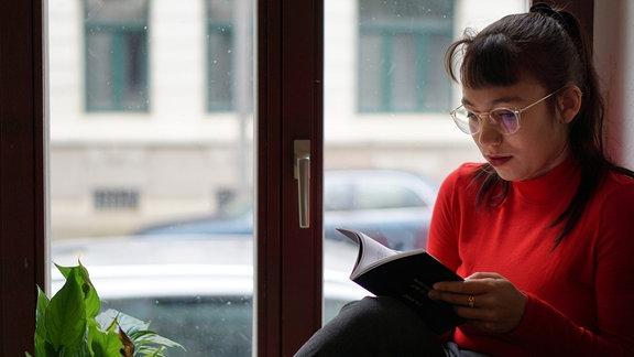 Die Autorin Ronya Othmann sitzt auf einer Fensterbank und liest