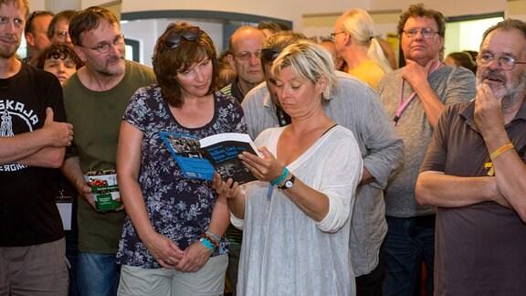 Besucher blättern im Buch