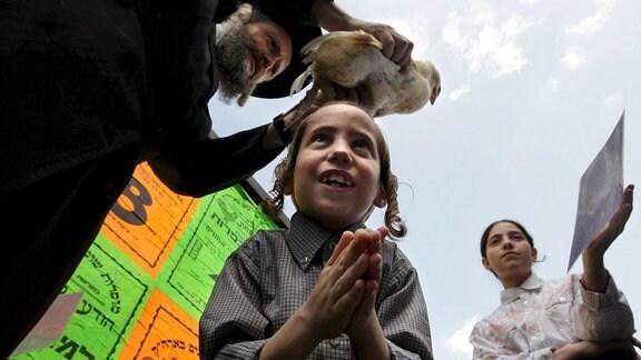Ein Mann schwenkt ein Huhn über dem Kopf eines betenden Kindes
