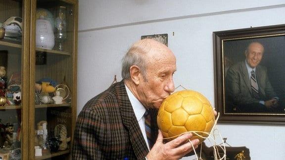 Der ehemalige Trainer der Fußball-Nationalmannschaft, Helmut Schön, küsst einen Fußball.