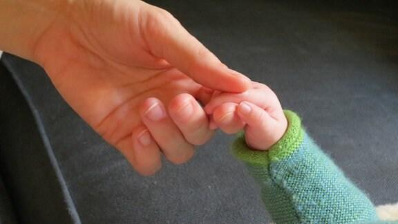 Hände von Baby und Hebamme