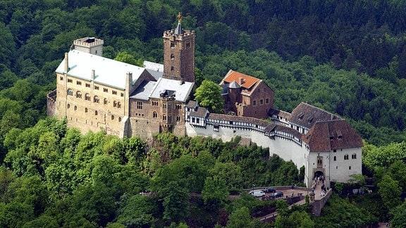 Zwischen sattgrünen Bäumen steht am 16.05.2003 die mehr als 900 Jahre alte Wartburg bei Eisenach