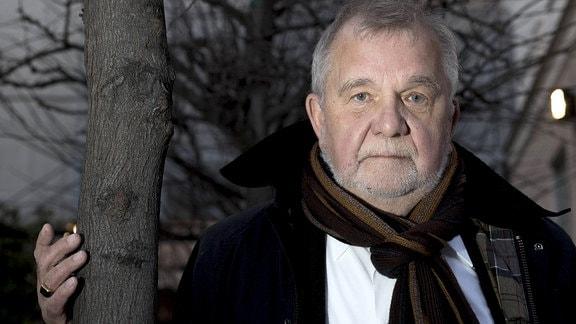 Der deutsche Philosoph Rüdiger Safranski steht an einen Baum gelehnt.