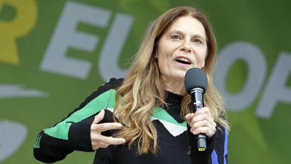 Eine Frau steht auf einer Bühne, im Hintergrund unscharf der Schriftzug Europa auf grünem Grund.