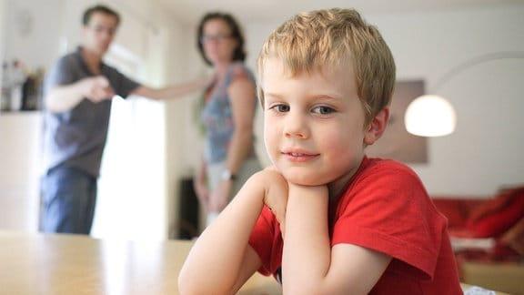 Ein Junge mit seinen streitenden Eltern