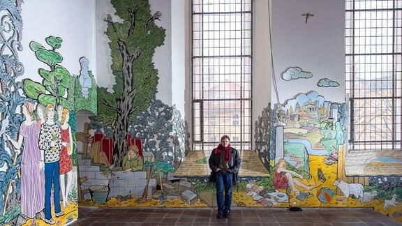 Der Maler und Grafiker Moritz Götze aus Halle/Saale steht am 23.03.2016 in der Schlosskirche St. Aegidien in Bernburg (Sachsen-Anhalt) an seinem Bilderzyklus mit biblischen Szenen aus Emailletafeln.